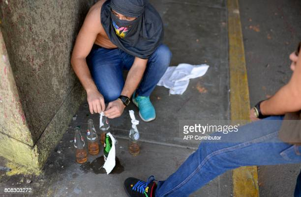 Protesters prepare molotov cocktails during a demonstration against the government of President Nicolas Maduro in Caracas on July 4 2017 A political...