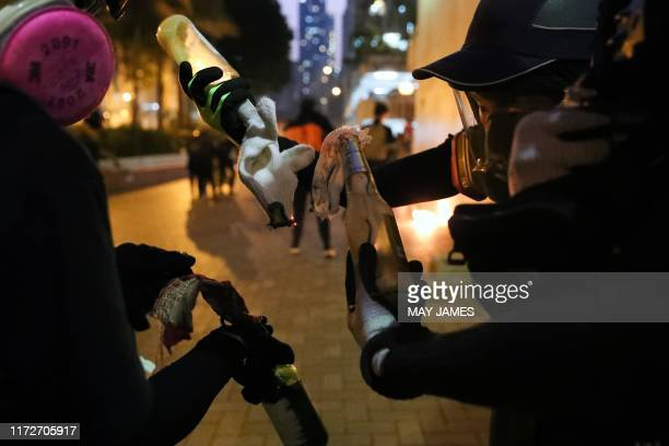 Protesters prepare Molotov cocktails in the Sham Shui Po district of Hong Kong on October 1 as violent demonstrations take place in the streets of...