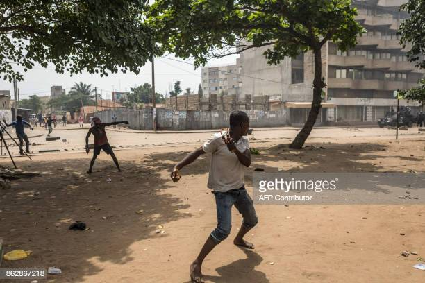 Protesters prepare to throw rocks as they face security forces during clashes as part of an anti-government protest in Lome on October 18, 2017....