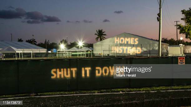 Protesters project phrases such as Shut It Down and Homes Instead from across the street at the detention facility for unaccompanied minors in...