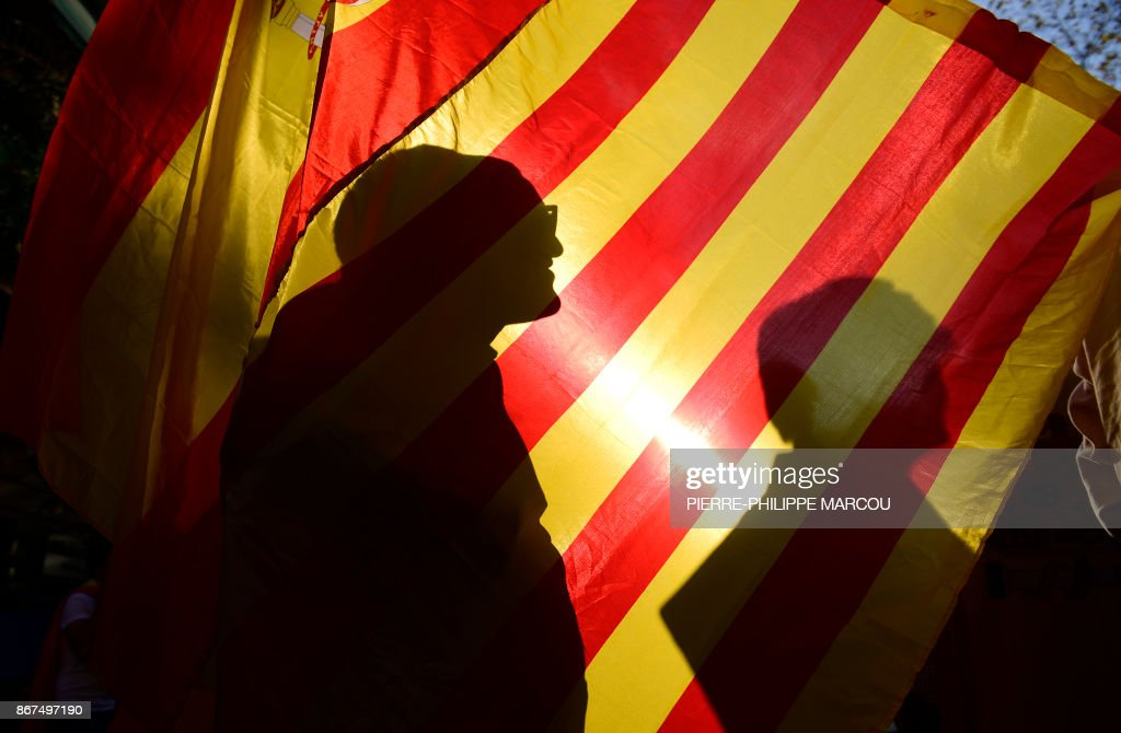 TOPSHOT - Protesters project their shadows on Spanish and Catalan flags during a demonstration calling for unity in Barcelona on October 28, 2017, a day after direct control was imposed on Catalonia over a bid to break away from Spain. Spain moved to assert direct rule over Catalonia, replacing its executive and top functionaries to quash an independence drive that has plunged the country into crisis and unnerved secession-wary Europe. /