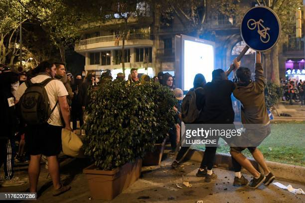 Protesters pull a traffic sign out during a demonstration called by the local Republic Defence Committees in Barcelona on October 16 after police...