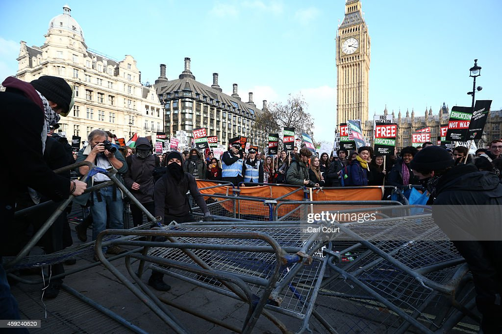 Protesters pull barriers apart in Parliament Square during a demonstration against fees and cuts in the education system on November 19, 2014 in London, England. A coalition of student groups have organised a day of nationwide protests in support of free education and to campaign against cuts. Photo by Carl Court/Getty Images)