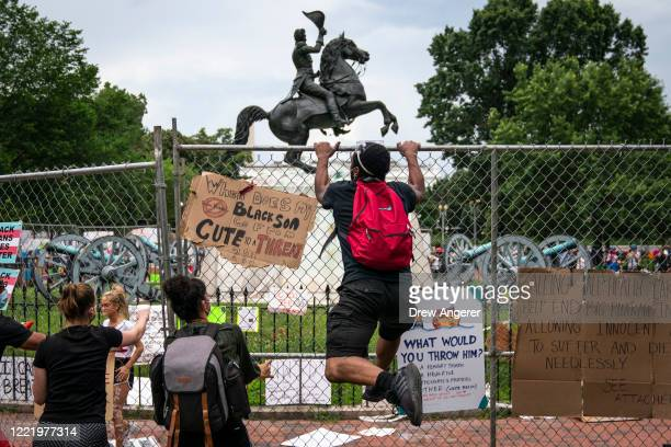 Protesters pull down a fence surrounding the statue of Andrew Jackson in an attempt to pull the statue down in Lafayette Square near the White House...