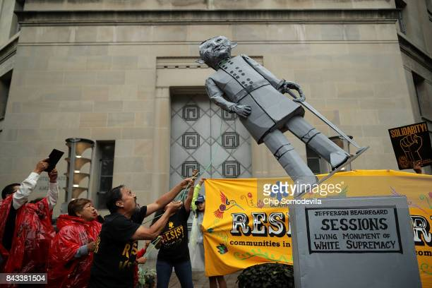 Protesters pull down a mock statue of Attorney General Jeff Sessions in front of the Department of Justice to demonstrate against the Trump...