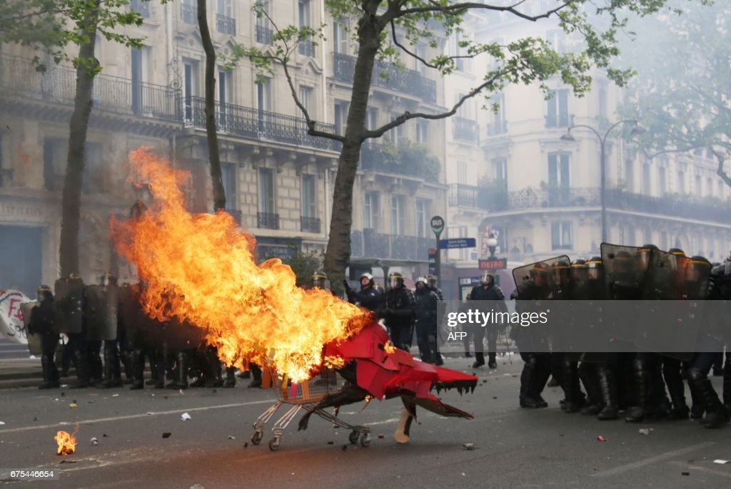 TOPSHOT - Protesters push a burning trolley towards French CRS anti-riot police officers during a march for the annual May Day workers' rally in Paris on May 1, 2017. / AFP PHOTO / Zakaria ABDELKAFI