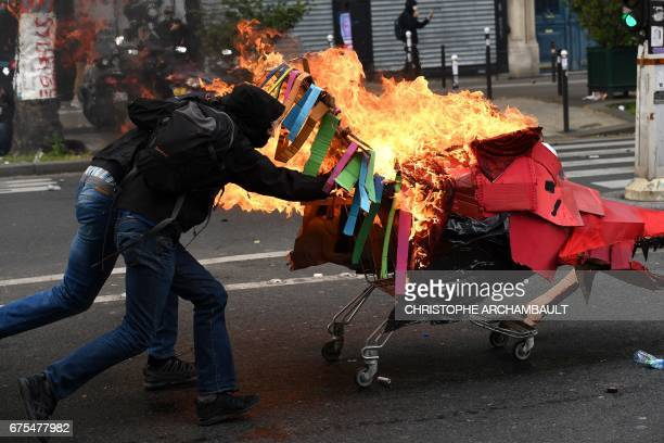 Protesters push a burning trolley towards French CRS antiriot police officers during a march for the annual May Day workers' rally in Paris on May 1...