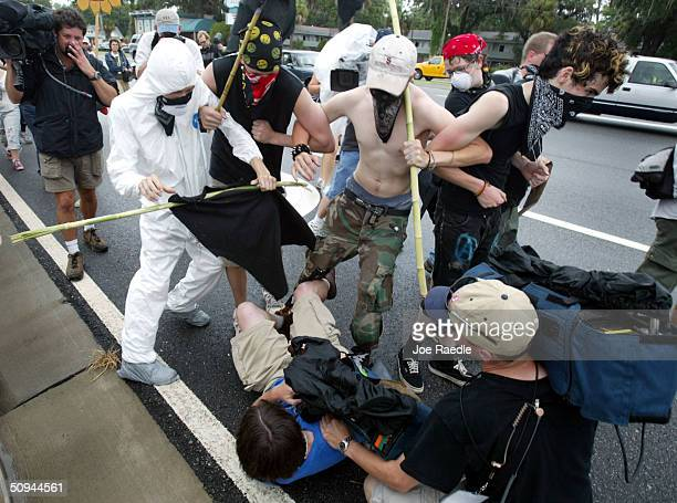 Protesters push over a television cameraman while yelling slogans against corporate media during a demonstration against the G8 Summit that is being...