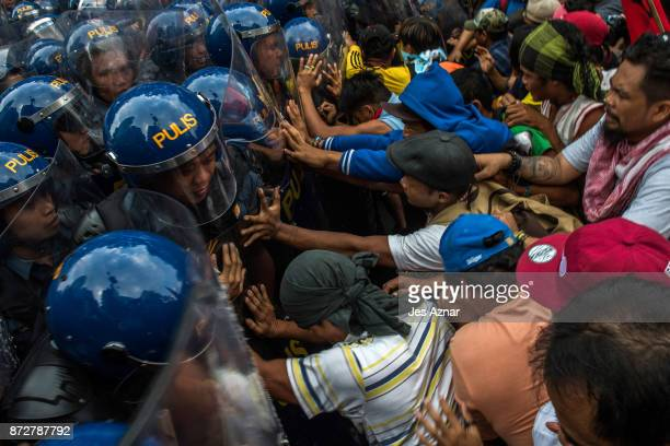 Protesters push their way through a phalanx of riot police a day ahead of US President Trump's arrival on November 11 2017 in Manila Philippines...
