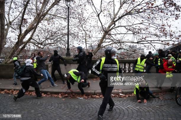 Protesters push through a gendarmes road block on the BirHakeim bridge in Paris on December 29 during a yellow vest antigovernment demonstration...