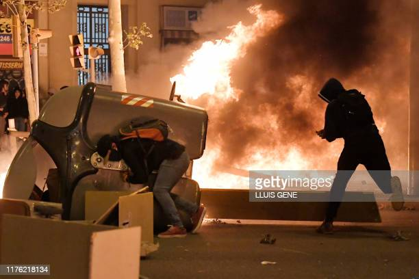 Protesters put barricades during a demonstration called by the local Republic Defence Committees in Barcelona on October 16 after police arrested 51...