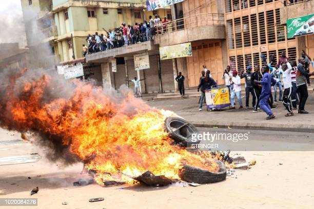 TOPSHOT Protesters put set a bonfire on a street to demand the release of the Ugandan politician Robert Kyagulanyi known as Bobi Wine who was...