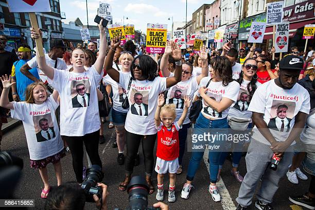Protesters put their arms in the air as they march to Tottenham Police Station to mark the fifth anniversary of Mark Duggan's death on August 6 2016...