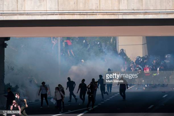 Protesters race away from tear gas after a march through Center City on June 1 2020 in Philadelphia Pennsylvania Demonstrations have erupted all...