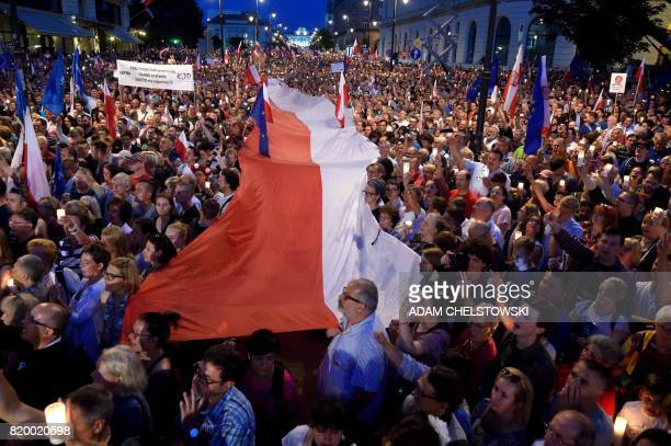 TOPSHOT Protesters raise candles and hold a Polish flag over the crowd during a protest on July 20 2017 in front of the presidential palace in Warsaw...