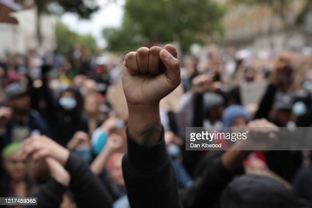 Protesters raise clenched fists during a Black Lives Matter protest outside the Houses of Parliament on June 3 2020 in London United Kingdom The...
