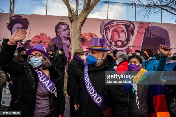 Protesters raise hands next to a feminist mural named 'Union makes force', during a protest against the removal of the mural proposed by far-right...