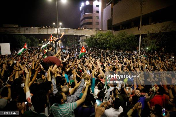 Protesters raise their arms and wave Jordanian national flags during a demonstration against a draft income tax law near the prime minister's office...