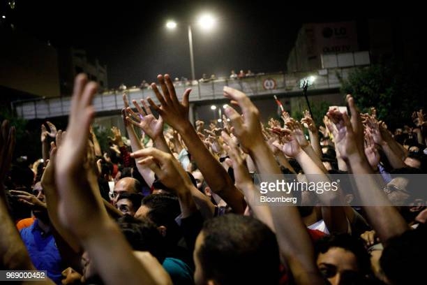 Protesters raise their arms during a demonstration against a draft income tax law near the prime minister's office in Amman Jordan on Wednesday June...