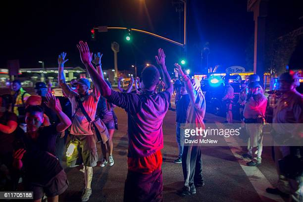 Protesters raise their arms near a line of deputies in riot gear during march in reaction to the fatal police shooting of unarmed black man Alfred...