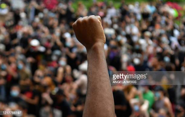 """Protesters raise their fists as they gather for a """"Black Lives Matter"""" demonstration in front of Borough Hall on June 5, 2020 in Brooklyn, New York...."""