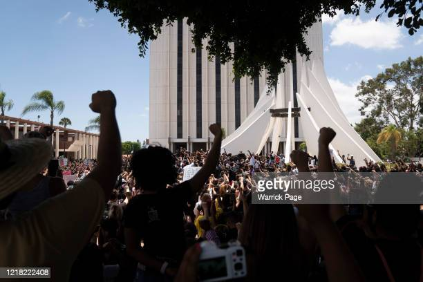 Protesters raise their fists at the Martin Luther King Jr. Memorial during a 'peace ride' with The Compton Cowboys for George Floyd on June 7, 2020...