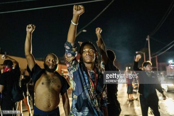 Protesters raise their fists during a demonstration against the shooting of Jacob Blake in Kenosha, Wisconsin on August 26, 2020. - Two people were...