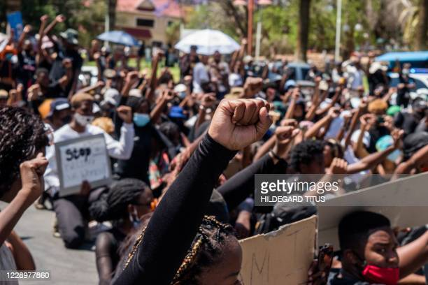 Protesters raise their fists during the second day of the #ShutItDown Protests, where hundreds of Namibian youth protested against gender-based...