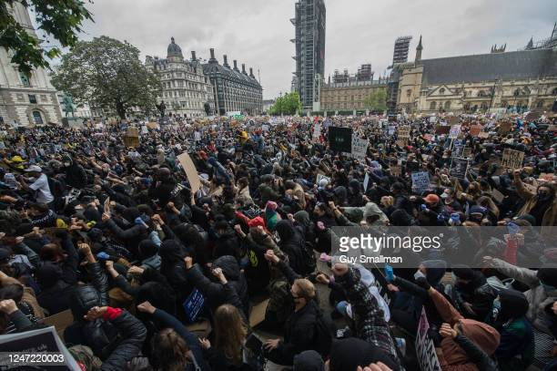 Protesters raise their fists in the air as they gather in Parliament Square for a rally as thousands of people join a Black Lives Matter protest on...