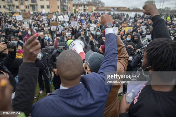 Protesters raise their fists in the air in front of the Brooklyn Center police station over the police killing of Daunte Wright in Brooklyn Center,...