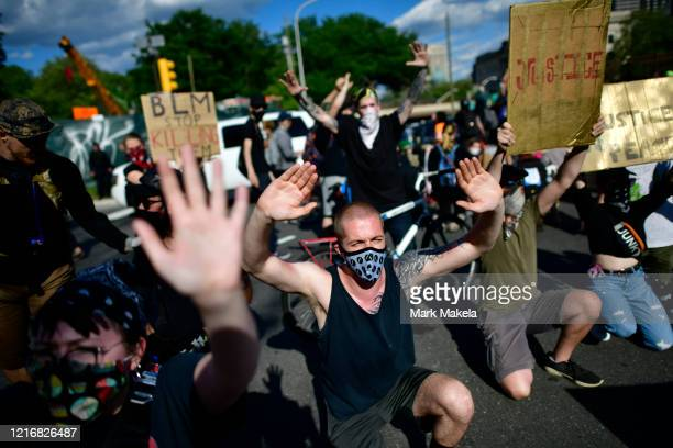 Protesters raise their hands in front of a police line after being shot by tear gas following a march on June 1 2020 in Philadelphia Pennsylvania...