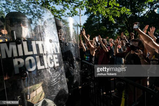 Protesters raise their hands to military police during a demonstration on June 1 2020 in Washington DC Thousands of protesters took to the streets...