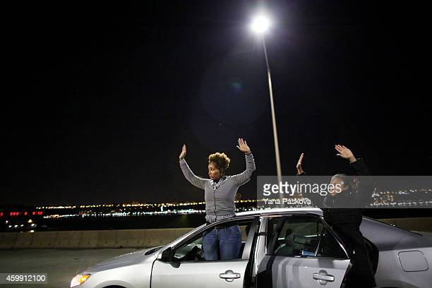 Protesters raise their hands to police on the West Side Highway December 3 2014 in New York Protests began after a Grand Jury decided to not indict...