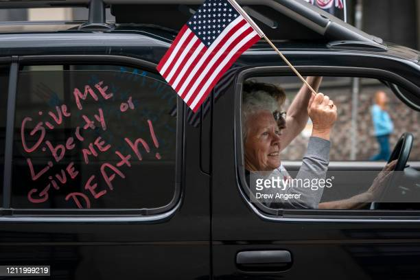 Protesters rally from their cars as they call for the state to lift stay-at-home orders and reopen the economy in downtown Richmond, Virginia near...