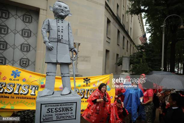 Protesters rally in front of the Department of Justice before pulling down a mock statue of Attorney General Jeff Sessions to demonstrate against the...