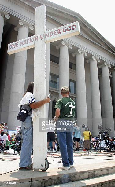 Protesters rally outside the state judicial building where workers earlier carted away the 2 1/2 ton Ten Commandments monument at the center of a...