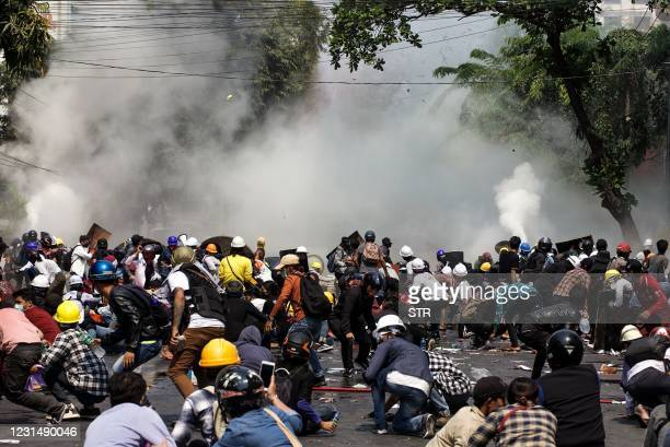 Protesters react after police fired tear gas during a demonstration against the military coup in Mandalay on March 3, 2021.