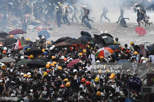 Protesters react after police fired tear gas during a rally against a controversial extradition law proposal in Hong Kong on June 12 2019 Violent...