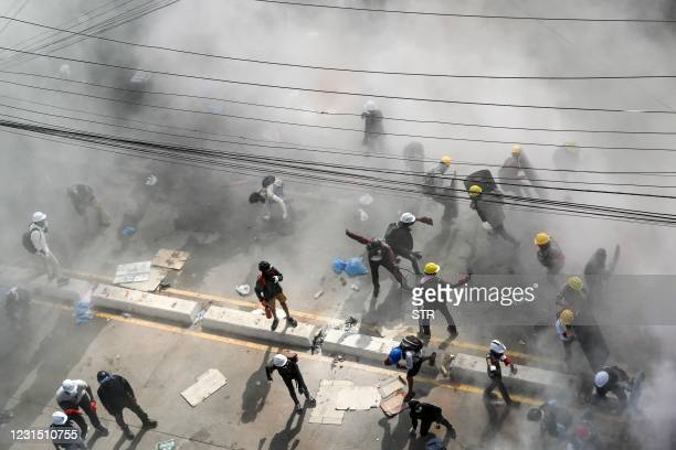 Protesters react after tear gas was fired by security forces in an attempt to disperse them during a demonstration against the military coup in...