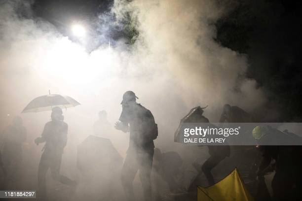 Protesters react amongst tear gas canister during clashes with police at the Chinese University of Hong Kong in Hong Kong on November 12 2019 Hong...