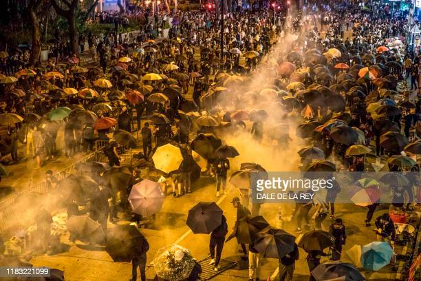 Protesters react as police fire tear gas while they attempt to march towards Hong Kong Polytechnic University in Hung Hom district of Hong Kong on...