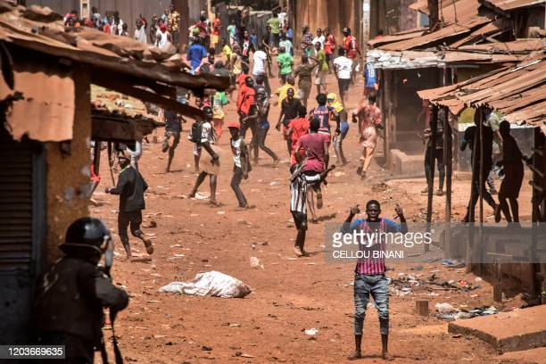 Protesters react as police throw rocks and fire tear gas in the opposition stronghold of Wanindara a northern suburb of Conakry on February 27 2020...
