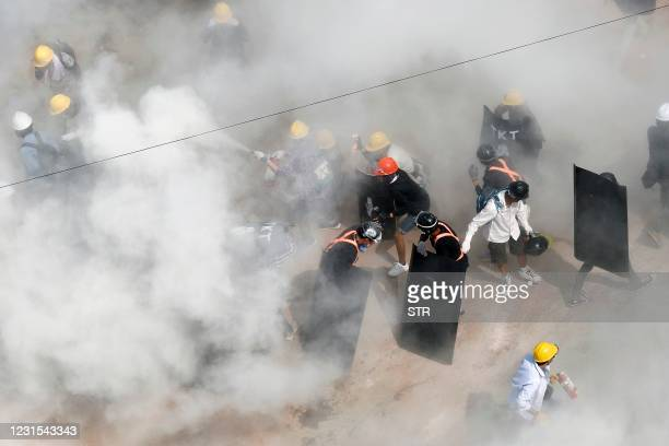 Protesters react as they are engulfed by tear gas fired by police, and as other demonstrators let off fire extinguishers, during a demonstration...