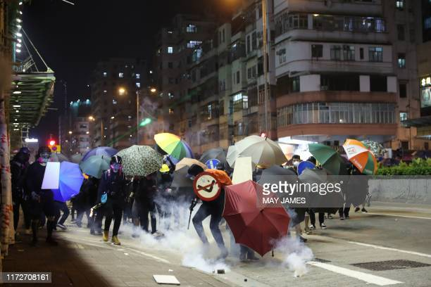 Protesters react from tear gas fired by riot police in the Sham Shui Po district of Hong Kong on October 1 as violent demonstrations take place in...