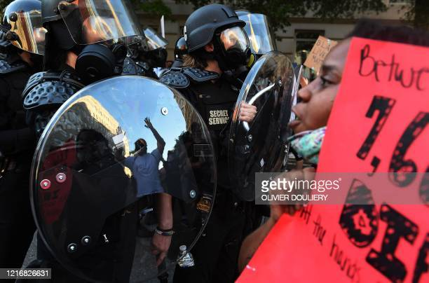 A protester's reflexion is seen whith hands up in the shield of police officers during a demonstration against the death of George Floyd at a park...