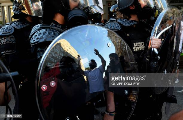 TOPSHOT A protester's reflexion is seen whith hands up in the shield of police officers during a demonstration against the death of George Floyd at a...