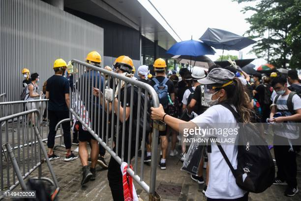 Protesters remove barricades during a demonstration outside the Legislative Council Complex in Hong Kong on June 12 2019 Violent clashes broke out in...