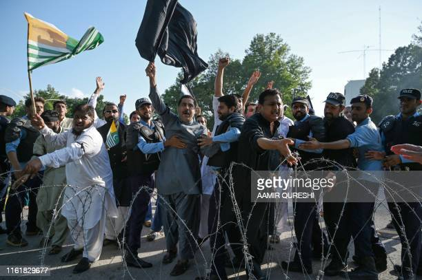 Protesters remove the barbard wire as they try to reach the Indian High Commission during a protest rally in Islamabad on August 15 as the country...