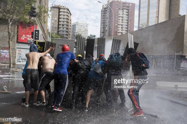 Protesters resist police vehicle throwing water as hundreds of protesters gather in Santiago to inflict improvements in the constitution and...