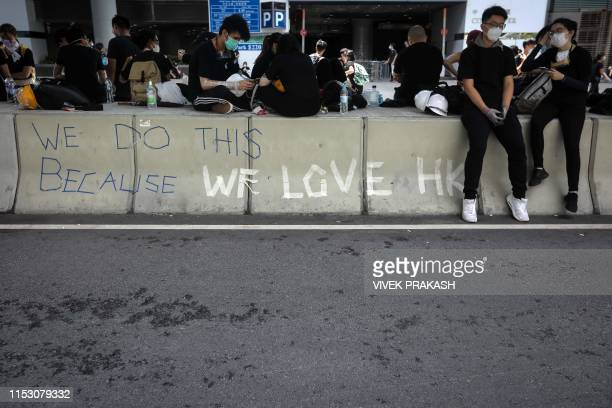 Protesters rest on a road divide outside the Legislative Council in Hong Kong after a flag raising ceremony to mark the 22nd anniversary of the...